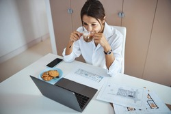 Beautiful woman using laptop and drinking latte at work
