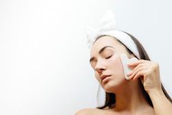 Beautiful woman using Natural Gouache Scraper Massager over face skin. Beautiful Caucasian Woman Using Gua Sha scraper over skin. beauty face skin care.