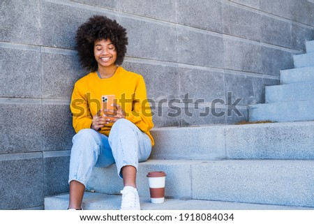 Beautiful Woman Using Phone Walking On Street. Portrait Of Stylish Smiling Business Woman In Colored Clothes Talking On Mobile Phone Near Office. Female Business. African And Afroamerican Ethnicity. Stock photo ©