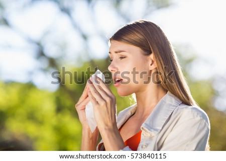 Beautiful woman using tissue while sneezing in park