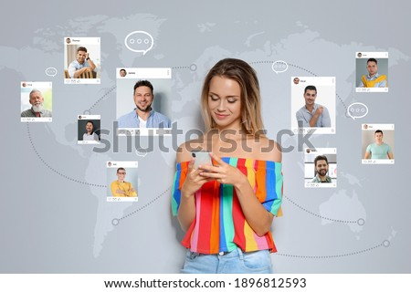 Beautiful woman visiting online dating site via smartphone on light grey background Stock photo ©