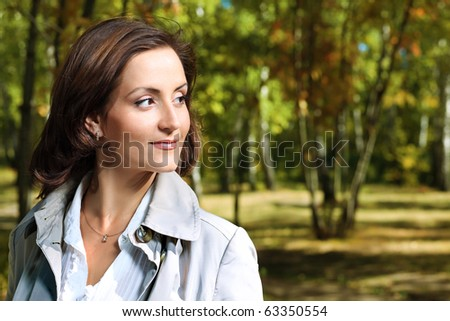 Beautiful woman walking at the autumn park.