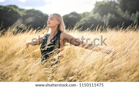 Beautiful woman walking in a wheat field and breathing deep #1150111475