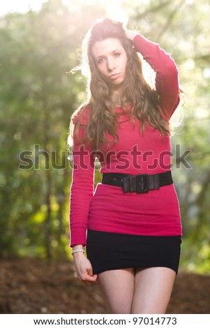 Beautiful woman walking in the park with back-lighting