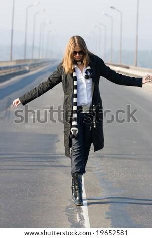 Beautiful woman walking on traffic line