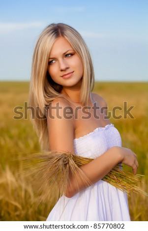 beautiful woman walking on wheat field