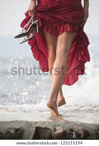 Beautiful woman walks at the sea side. Wet, red dress, high heels shoes.