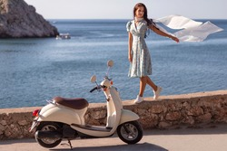 Beautiful woman walks on the seashore of her scooter. Travel  concept.