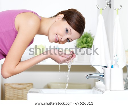 Beautiful woman washing her face by clean water standing in bathroom