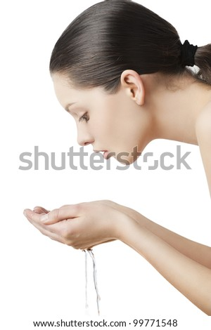 Beautiful woman washing her face isolated on white with wet hair and natural make up, she is turned in profile and looks the water in her hands