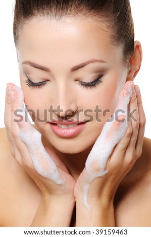 Beautiful woman washing her face with foam on the hands