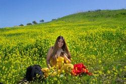 beautiful woman watching her social networks on her cell phone on a picnic in a landscape full of flowers