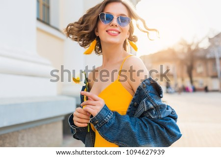 beautiful woman waving hair smiling, stylish apparel, wearing denim jacket and yellow top, fashion trend, summer style, happy positive mood, sunny day, sunrise, street fashion, blue sunglasses