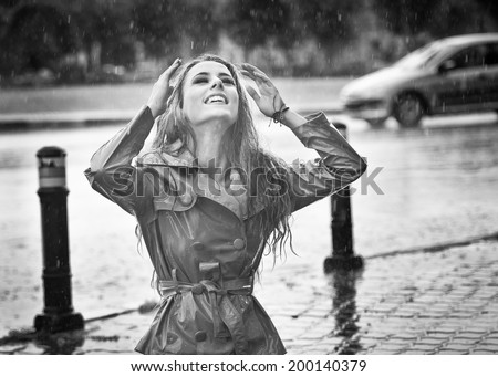 Beautiful woman wearing a coat posing in the rain. Happy long hair girl enjoying the rain drops in the park, outdoor shot. Attractive female relaxing in a rainy day. Black and white photo
