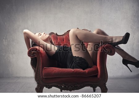 Beautiful woman wearing a nightgown and lying on an armchair