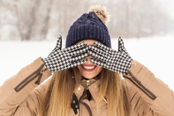Beautiful woman wearing a warm winter clothes, hiding her eyes with hands in gloves, enjoying a snowy winter day in nature