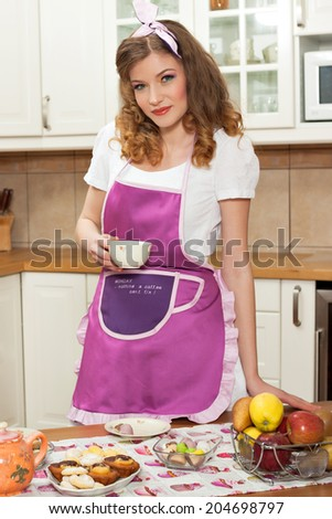 Beautiful woman wearing an apron holding a tea or coffee cup in the kitchen with cookies, pralines and fruits in front of her; woman wearing a kitchen apron saying \