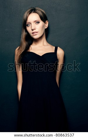 beautiful woman wearing black dress over dark background