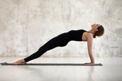 Beautiful woman wearing black sportswear practicing yoga, standing in Purvottanasana pose on mat, doing Upward Plank exercise, sporty girl working out at home or in yoga studio with grey walls