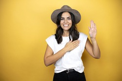 Beautiful woman wearing casual white t-shirt and a hat standing over yellow background smiling swearing with hand on chest and fingers up, making a loyalty promise oath