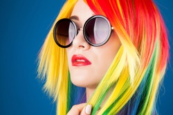 beautiful woman wearing color wig and sunglasses against blue background