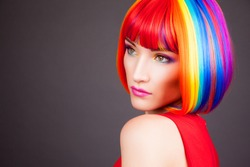 beautiful woman wearing colorful wig against gray background