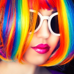 beautiful woman wearing colorful wig and white sunglasses against wooden background