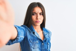 Beautiful woman wearing denim shirt make selfie by camera over isolated white background skeptic and nervous, frowning upset because of problem. Negative person.