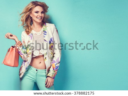 Shutterstock Beautiful woman wearing nice clothes, handbag posing on turquoise background. Fashion spring photo