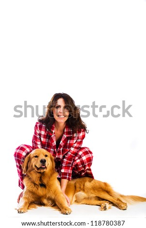 Beautiful woman wearing red flannel pajamas with her handsome golden retriever dog. - stock photo