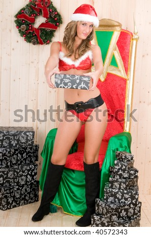 beautiful woman wearing santa claus clothes with present