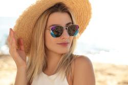 Beautiful woman wearing sunglasses outdoors on sunny day