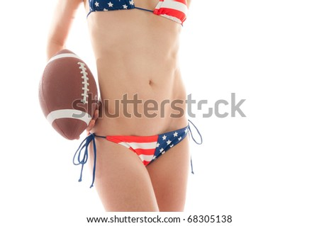 Beautiful woman wearing the United States flag bikini holding a football isolated over white background