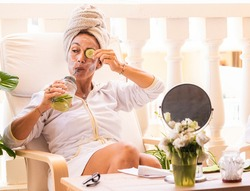 Beautiful woman wearing white bathrobe with cucumber skin care mask while drinking detox drink. DIY home spa