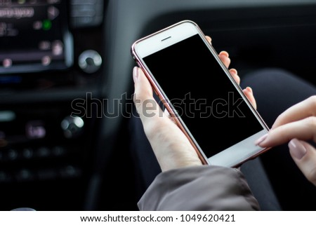 Beautiful woman while sitting on the front passenger seats in the car. Girl is using a smartphone. Hand closeup