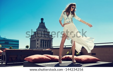 Beautiful woman white loose skirt, high heels, and jeans jacket standing on the bed on the rooftop