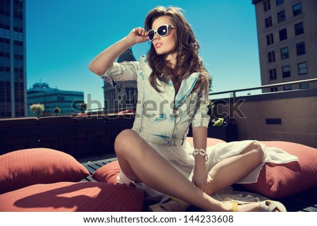Beautiful Woman White Skirt, High Heels, And Jeans Jacket Sitting The Bed On The Rooftop