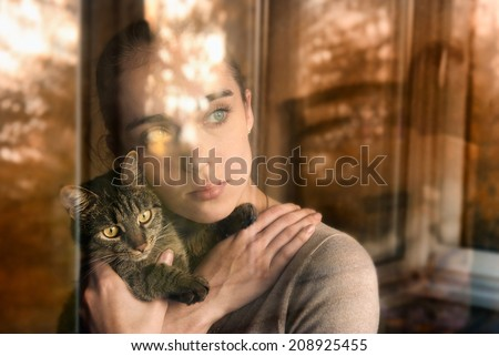 Beautiful woman with a cat and sits by the window