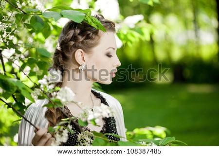 Beautiful woman with a hair braid and stylish make-up on the background of a blossoming park.