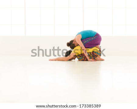 beautiful woman with a handsome man dressed in vibrant colors are partners yoga in white gym