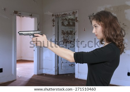 Beautiful woman with a loaded handgun pistol #271510460