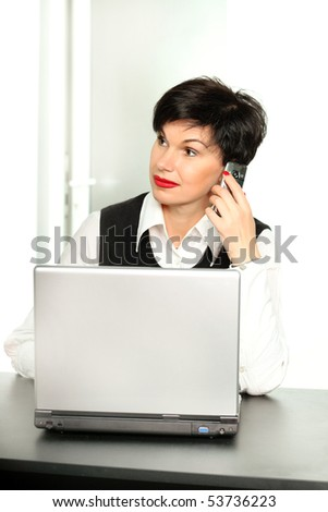 Beautiful woman with a mobile phone and a laptop