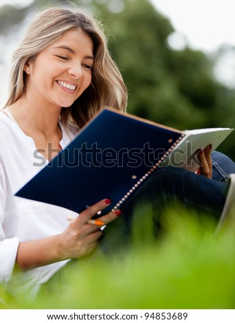 Beautiful woman with a notebook studying at the park