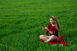 Beautiful woman with a phone in her hands sits on the grass. The girl looks at herself in the camera of the phone and takes selfie photos. She smiles and enjoys a warm day. Concept photo on smartphone