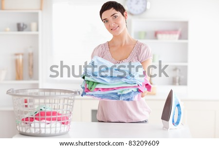 Beautiful Woman with a pile of clothes in a utility room