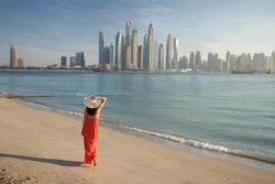 Beautiful woman with a red dress and a white hut is walking on the beach in Dubai. In the background there is the skyline from Dubai Marina