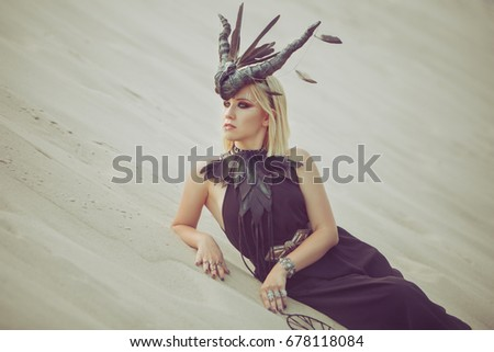 Beautiful woman with animal horns on her head, lying on the sand in the desert. #678118084