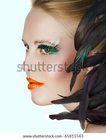 beautiful woman with artistic gold and orange lips and green eyelashes with feathers on white background