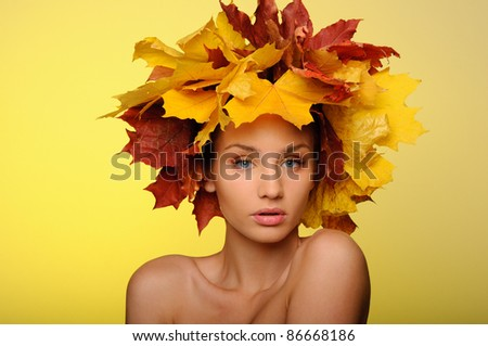 Beautiful woman with autumn leaves on yellow background