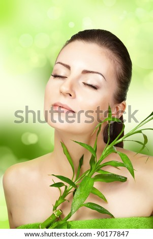 Beautiful woman with bamboo plant on a green background. SPA